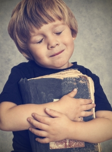 Little boy hugging an old book, he is happy